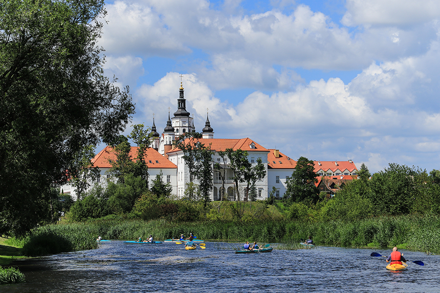 Group of people canoeing on the Narew river at the bottom of the